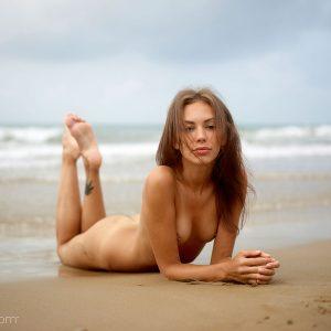 Karina pose nue sur une plage naturiste