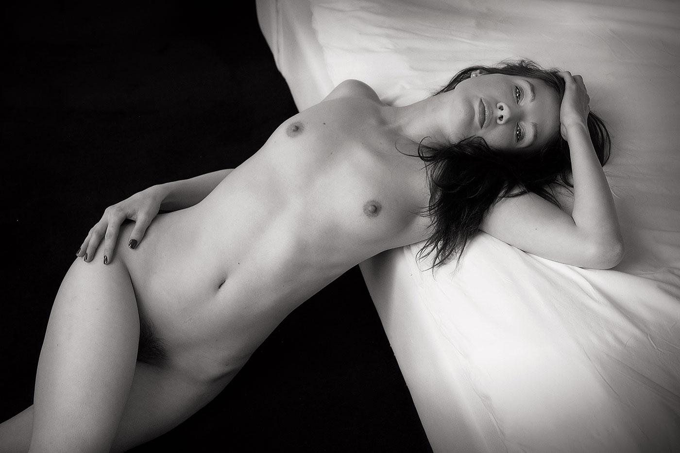 Jeune femme nue près du lit